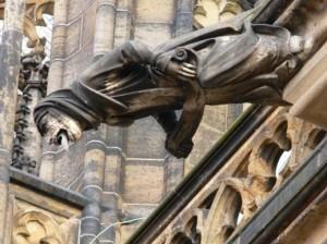 Un gargoyle di forma umana si estende dalle grandi pareti esterne della cattedrale di Praga
